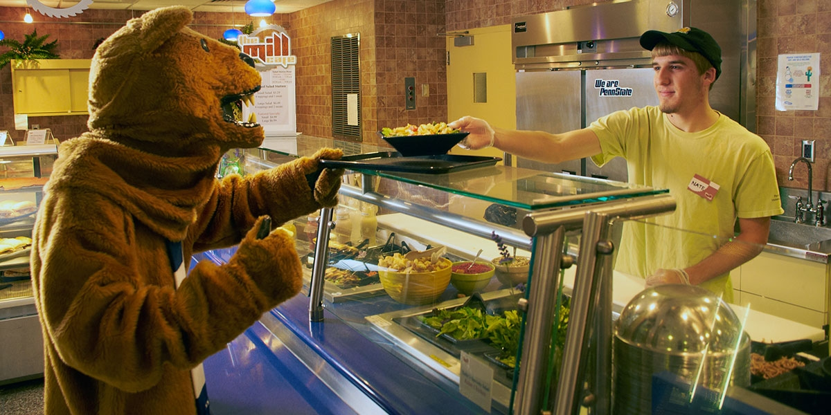Lion getting lunch from student employee